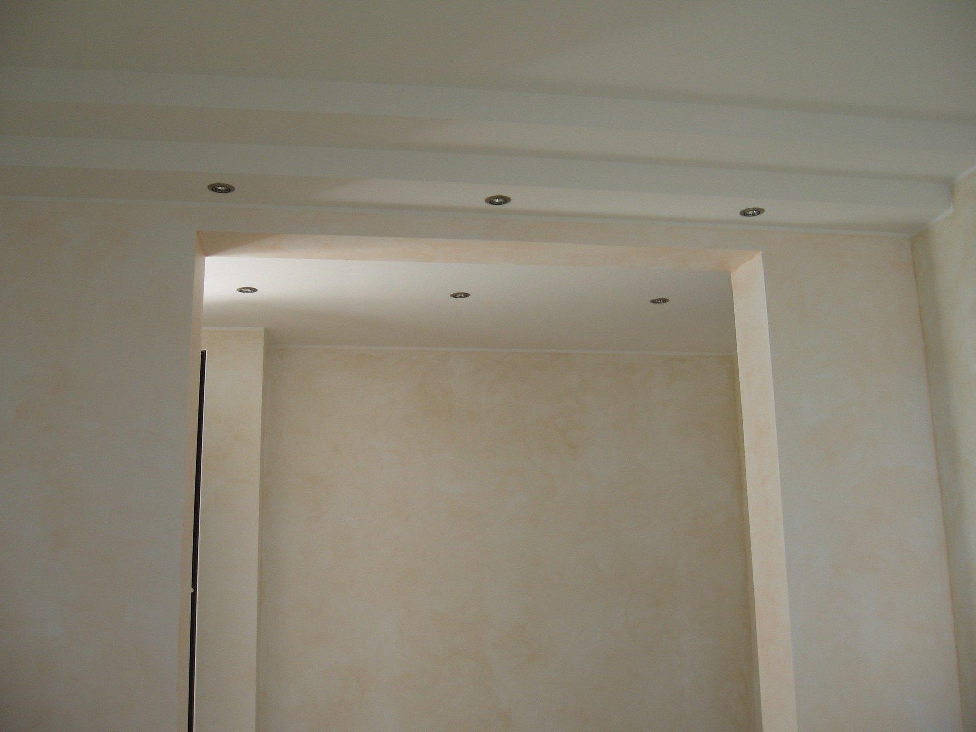 Stanza dipinta di bianco con installazione di luci alogene nel tetto