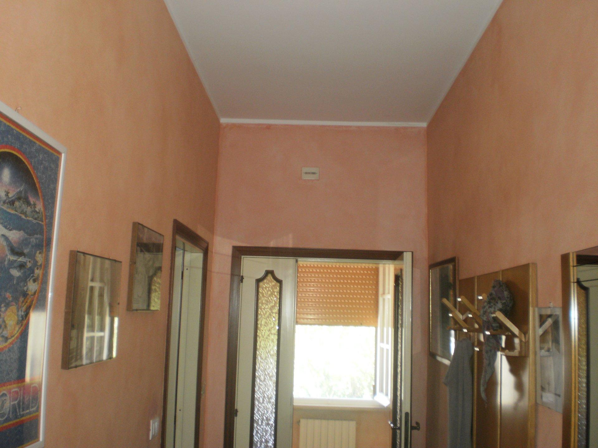 Ingresso e corridoio di una casa dipinto di colore salmon