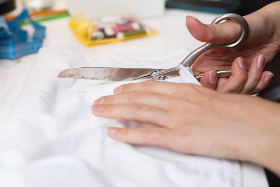 una mano con una forbice che taglia una stoffa