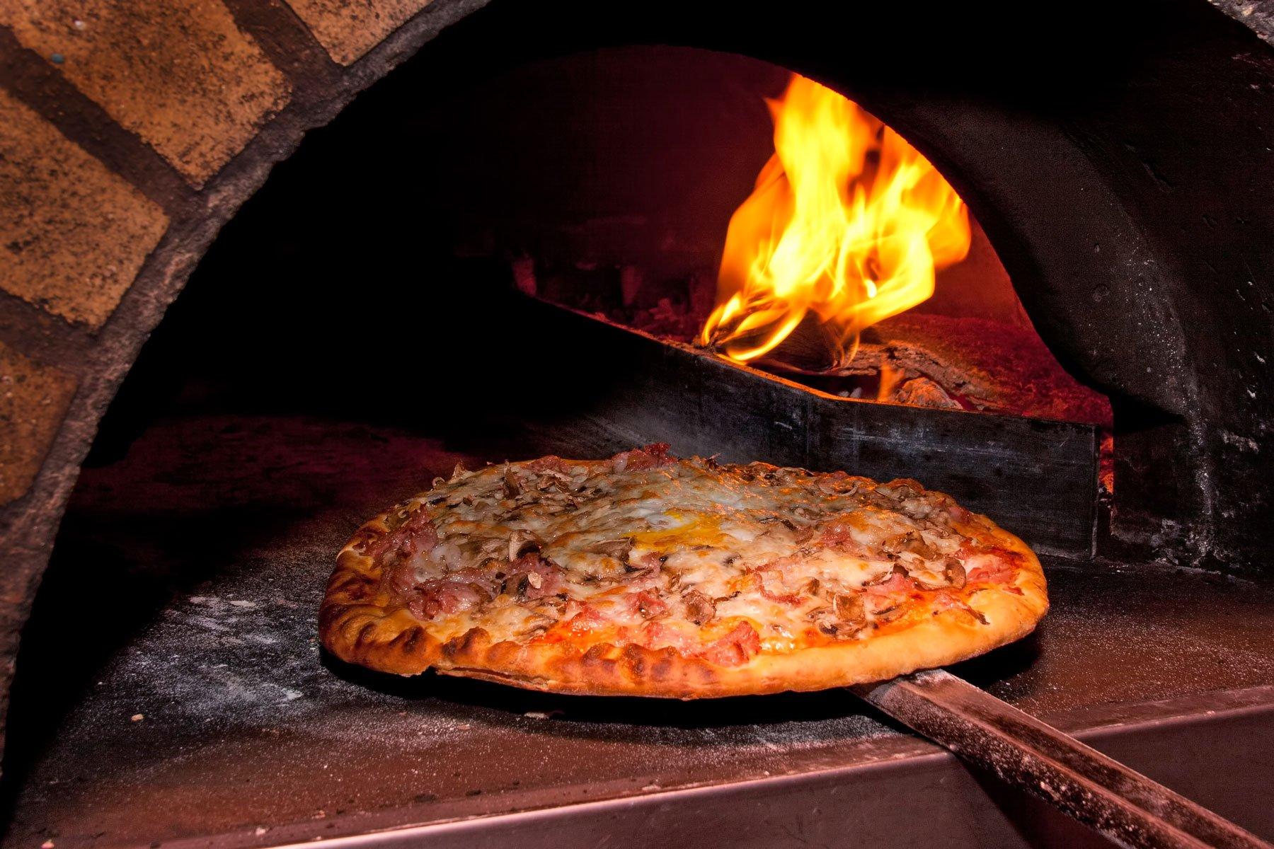 Pizza prosciutto e funghi cotta in forno a legna