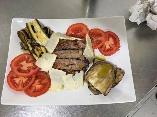 costata di vitello alla brace con zucchine grigliate, pomodori e grana
