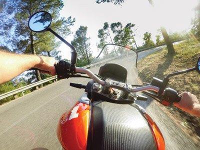 Mani guidando una motocicleta sulla strada a Pieve Emanuele, Milano