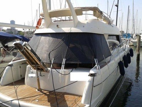 Chiusura pozzetto barca a motore in sunbrella americano o rete ombreggiante, completa di finestrature e copri vetri.