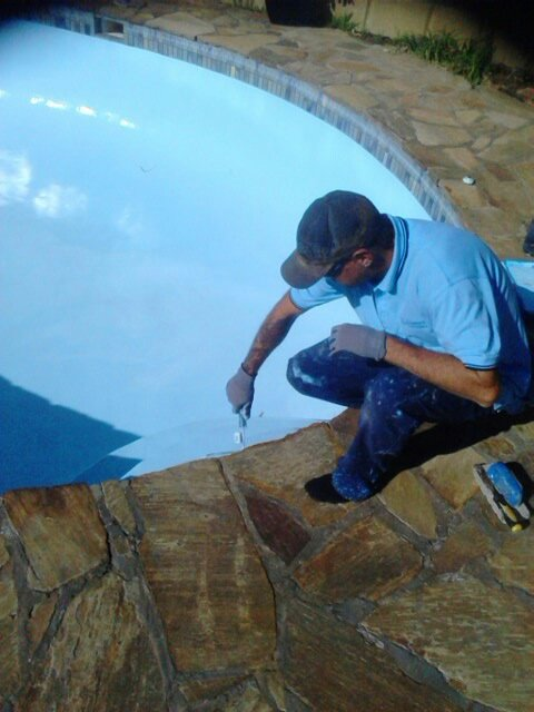worker painting pool wall in perth