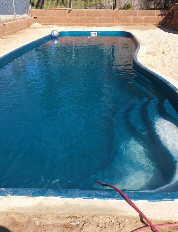 filled swimming pool being cleaned in perth