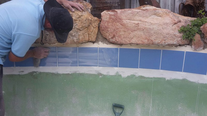 worker cleaning swimming pool tile
