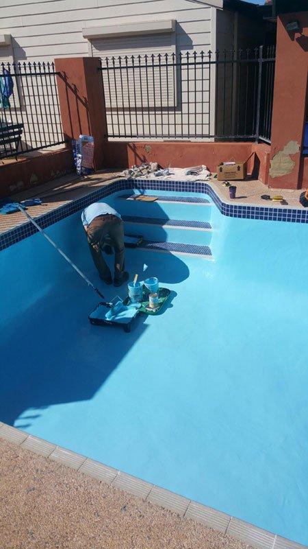 worker painting pool floor
