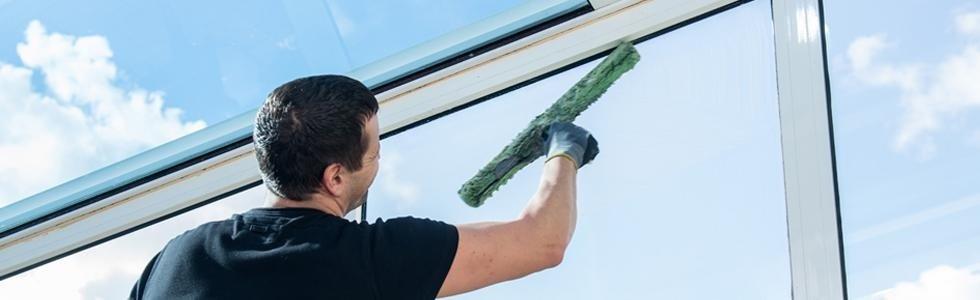 addetto mentre pulisce delle vetrate