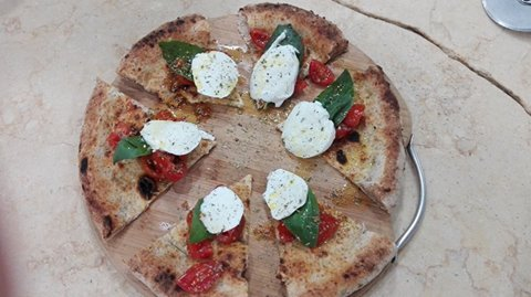 Pizza bianca con pomodori freschi, rucola e mozzarella di bufala