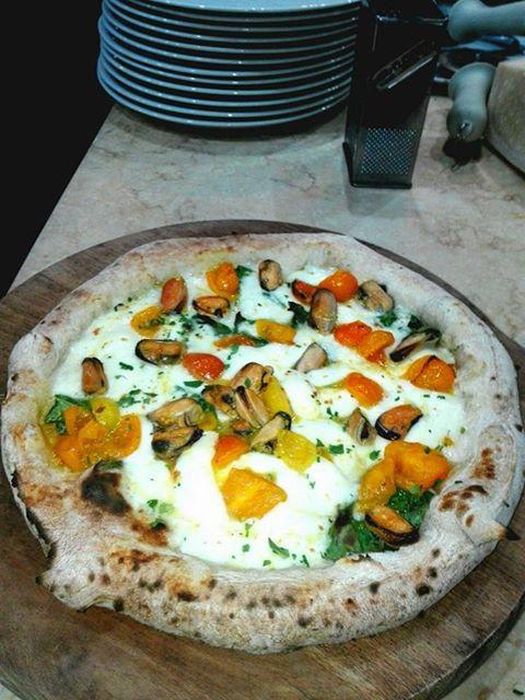 Pizza bianca con pomodori freschi, cozze e formaggio