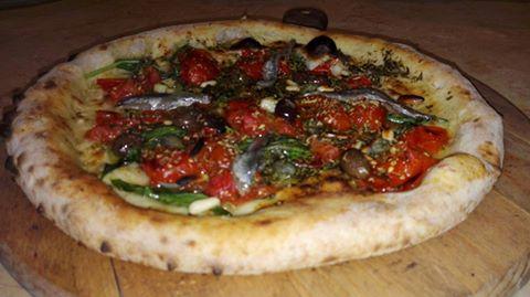Pizza bianca con acciughe, pomodori freschi, olive nere e zucchino