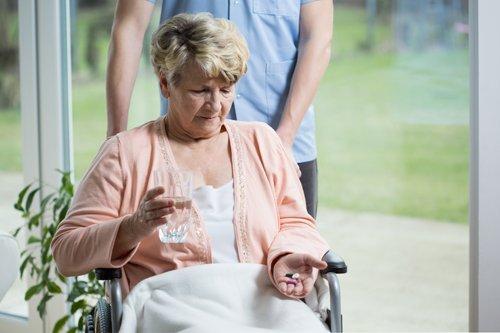 donna sulla sedia a rotelle si prepara a ingerire delle medicine tenute in mano