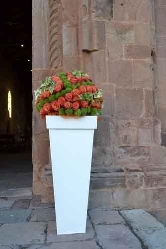 mazzo di rose rosse sopra una colonna davanti a una chiesa