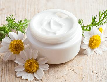 un barattolo di crema aperta con di fiori di camomilla accanto