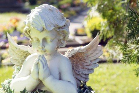 statua di un angelo in marmo come ornamento funebre in un cimitero