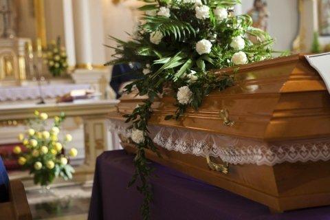 cofano funebre allestito con addobbi floreali in una chiesa