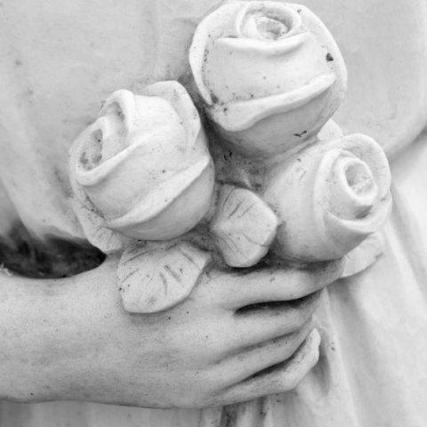 inquadratura della mano di una statua di marmo funebre che regge tre rose