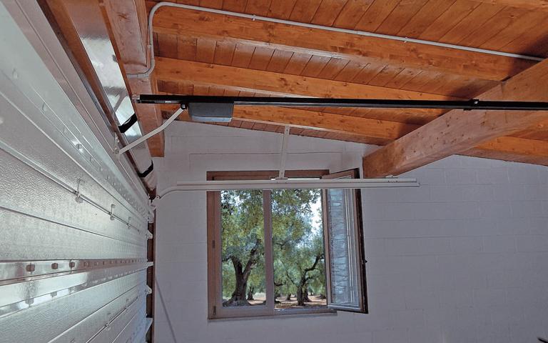 vista interna di un garage con soffitto in legno, finestra aperta  e porta sezionale