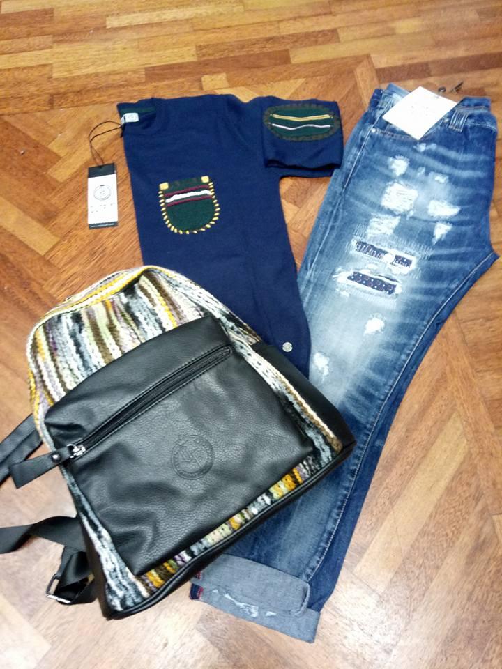 Un paio di jeans, una maglietta di color blu  e una borsa multicolore, il tutto appoggiato sul parquet