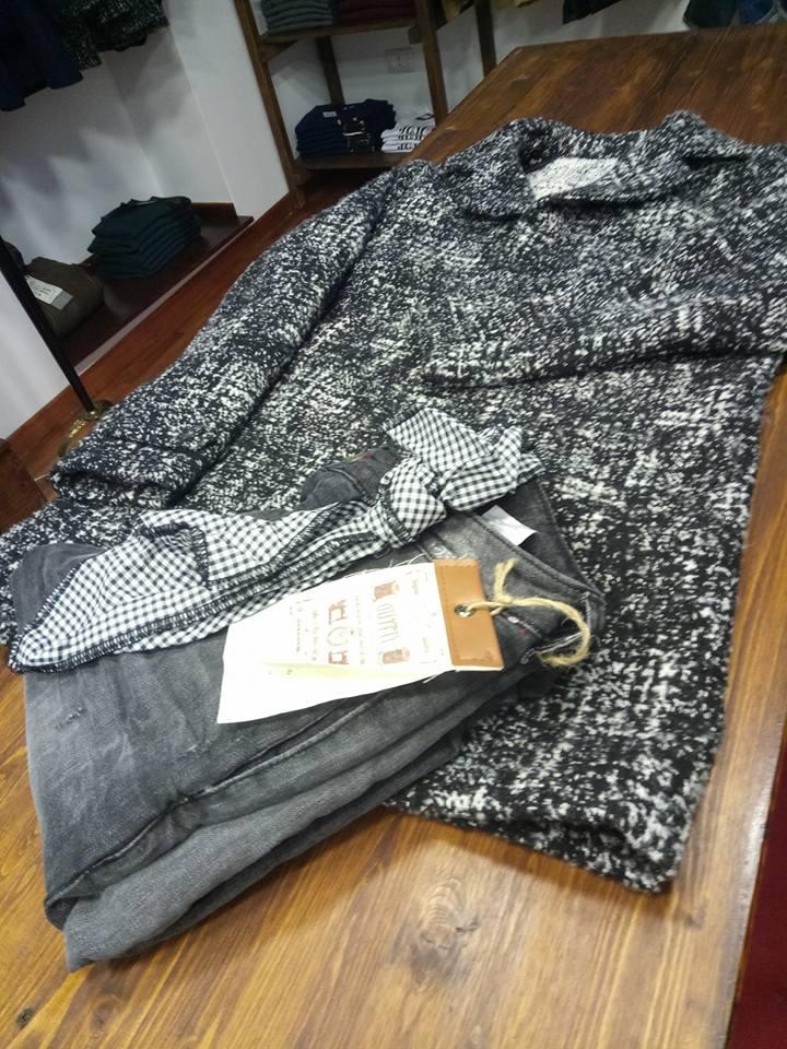 Un paio di jeans di color nero e una giacca di lana di color bianco e nero appoggiati su un tavolo di legno