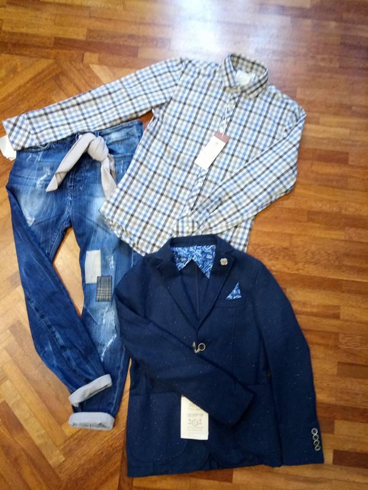 Un paio di jeans blu, una camicia a righe di color blu e marrone e una giacca blu appoggiata sul parquet