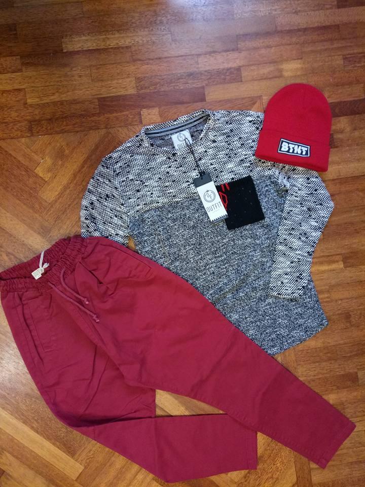 Pantaloni larghi di color rosso, una maglia di lana di color bianco e nero e un cappello di lana di color rosso esposto su un parquet