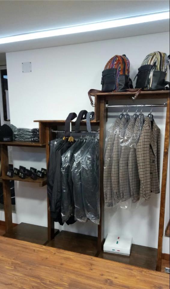 esposizione di giacche beige coperte da plastica  su un appendiabiti con rifiniture in legno e in alto degli zaini e una zucca luminosa