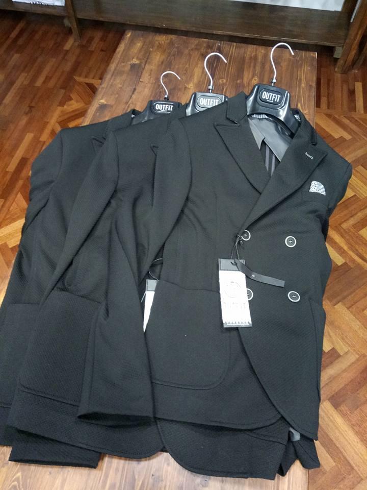 Tre giacche nere con appendini appoggiati sul pavimento in legno