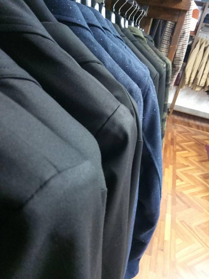 Una mensola con dei jeans piegati di color blu e nero, appendiabiti con delle giacche di color nero, blu, verde e  altri a disegni di sacchi