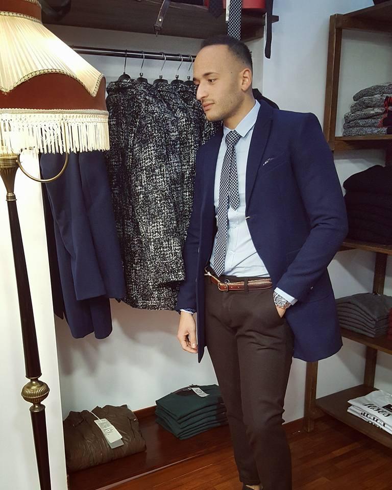 Un uomo con pantaloni marroni, camicia azzurra, cravatta a scacchi e la giacca blu in posa davanti all'appendiabiti e mensole con dell'
