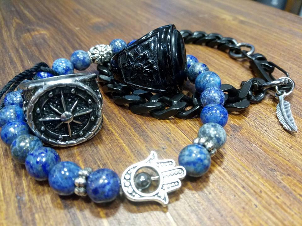 due braccialetti, uno a perline blu e l'altro nero con una piuma cromata attaccata e un anello di metallo grigio scuro con disegnata una figura simile alla rosa dei venti