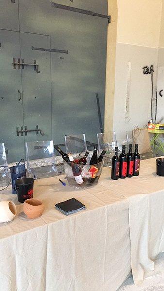 una tavola con una tovaglia bianca con sopra delle bottiglie di vino, alcune dentro a una grande bacinella di vetro e altre esposte in fila