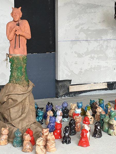 delle piccole statuette di cagnolini e gattini di diversi colori e una statua  raffigurante un uomo di color rosa