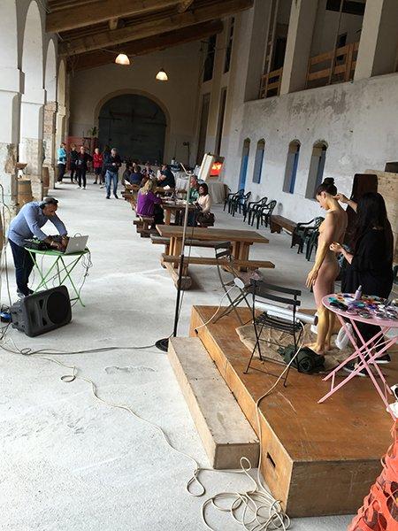 sotto un porticato un palco di legno con sopra due donne e di fronte un uomo al computer su un tavolino con delle cuffie