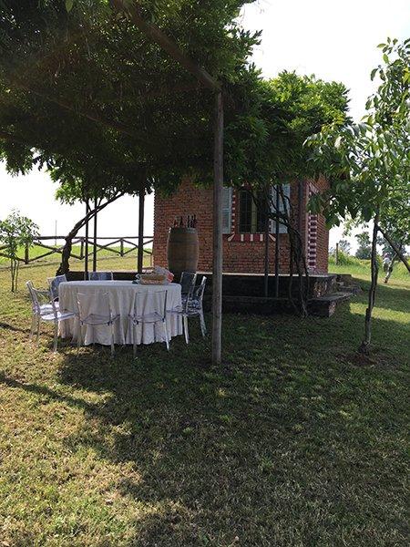 un tavolo rotondo con tovaglia bianca, dietro un barile di legno e una piccola casa con mattoni a vista in un prato con degli alberi