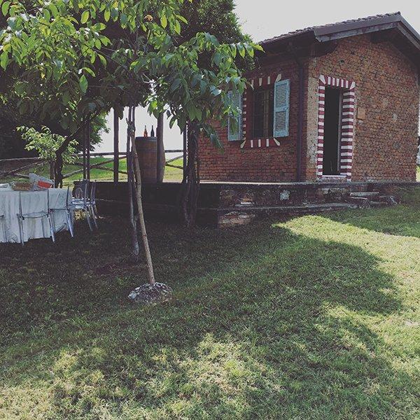 una piccola casa con mattoni a vista di color rosso in un prato con degli alberi e sulla sinistra un tavolo rotondo con una tovaglia bianca