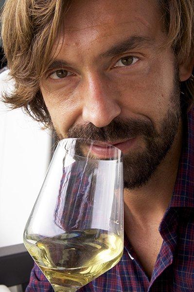 il volto del calciatore Andrea Pirlo che sta per degustare un vino bianco in un bicchiere
