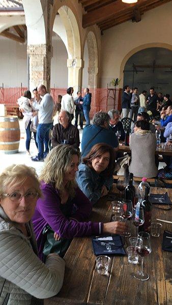delle persone sotto un portico sedute al tavolo con dei bicchieri di vino e bottiglie