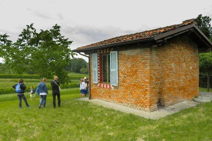 una piccola casetta con mattoni rossi a vista in un prato con degli alberi e delle persone in piedi vicino