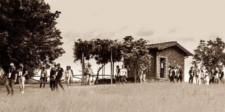 una foto in bianco e nero di persone che camminano in un prato con degli alberi e una casetta