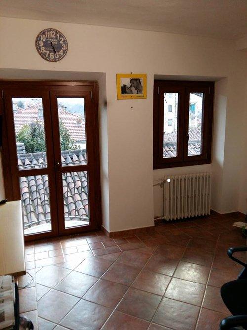 vista interna di una stanza con parete gialla e finestre