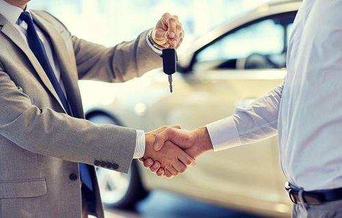 venditore di auto dando chiave della vettura per cliente