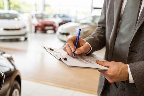 venditore di auto mentre scrive su un foglio