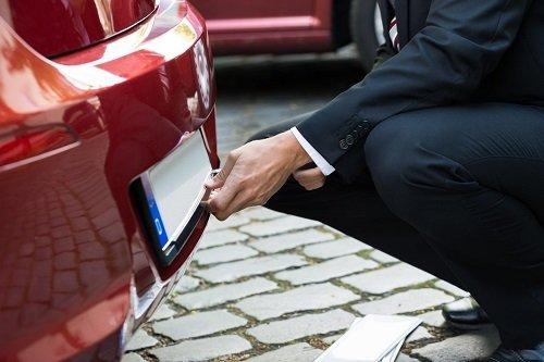 uomo vestito in abito formale toglie l`etichetta della targa di una macchina