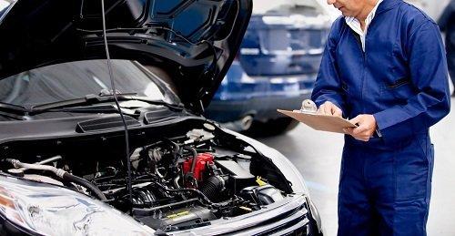 meccanico mentre controlla motore di una macchina