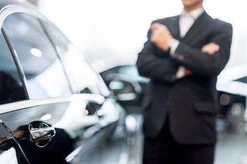 uomo vestito in abito formale con una macchina