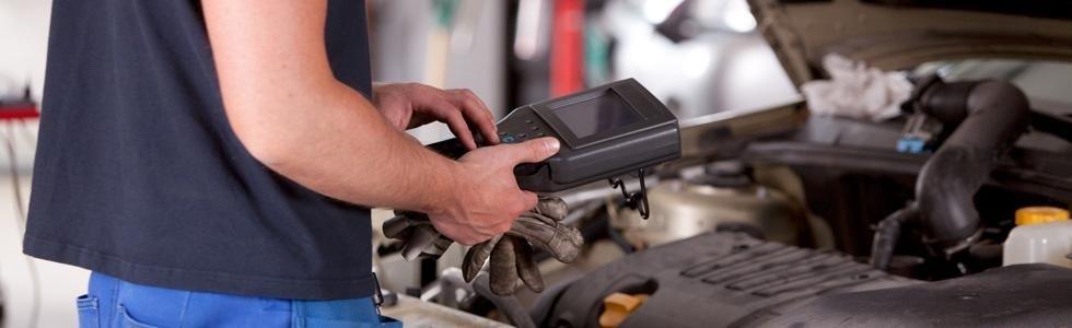 meccanico mentre lavora con strumento diagnostico in officina auto
