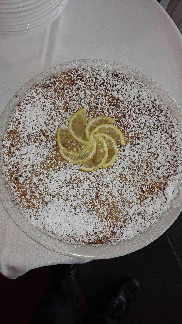 una torta con zucchero a velo e fette  di limone
