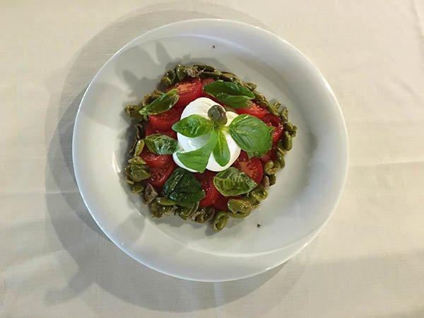 un piatto con pomodori, olive e mozzarella