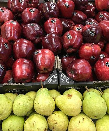 Primo piano di cassetti con succose pere gialle e rosse mele